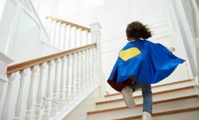 Girl Dressed Up As Superhero Playing Game On Stairs