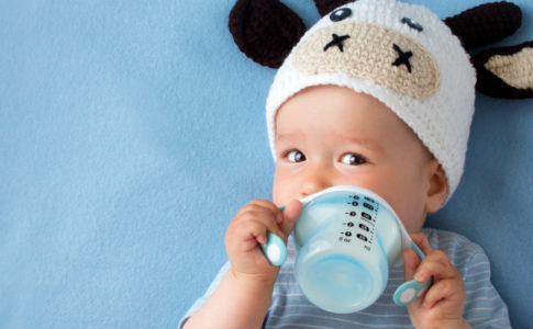 Toddler in cow hat with sippy cup